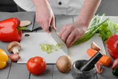 Cook dicing spring onions. On a cutting board. Cooking tasty and healthy meal using fresh vegetables stock photos