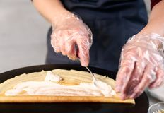 Cook in dish preparing process. Cropped female hands lubricate crepe with creamy sauce on black round plate. Front view. Cropped view of chef in blue apron in stock photos