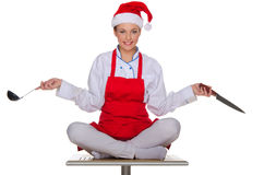 Cook with dishes in the cap of Santa Claus Royalty Free Stock Image