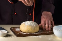 Cook with dough in a dark jacket. Cooking in the restaurant. Stock Photos