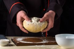 Cook with dough in a dark jacket. Cooking in the restaurant. Royalty Free Stock Photo