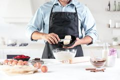 A cook with eggs on a rustic kitchen against the background of men`s hands Royalty Free Stock Images