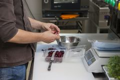Cook extracts bones from cherry berries stock images