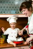 Cook family. Laughing mother and her little son in cook costume at the kitchen Royalty Free Stock Photography
