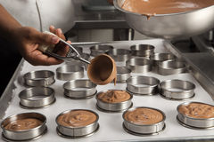 Cook filling the moulds with the chocolate mousse Stock Photos