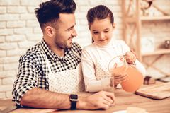 Girl with Carafe in Hands on Father Juice at Home. stock image