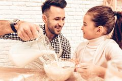Cook Food at Home. Happy Family. Father`s Day. Girl and Man Cooking. Man with Flour on Face. Spend Time Together. Food on Table. Pour Flour. Cook Dough. Pours royalty free stock photo