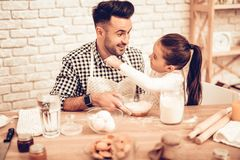 Cook Food at Home. Happy Family. Father`s Day. Girl and Man Cooking. Man with Flour on Face. Spend Time Together. Food on Table. Pour Flour. Cook Dough. Pour stock images