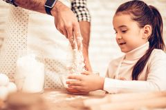 Cook Food at Home. Happy Family. Father`s Day. Girl and Man Cooking Smiling Man and Child at Table. Spend Time Together. Food on. Table. Break Egg in Bowl. Pour royalty free stock photography