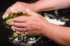 Cook forming dough into pasta noodles stock photos
