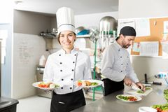 Cook With Fresh Food In Plates. Confident professional chef with chicken and vegetables in kitchen royalty free stock photography
