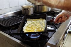 Cook fries pancake on a pan on a gas stove in the kitchen of a restaurant stock image
