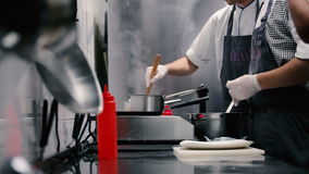 Cook fries pancakes. Second chef prepares the sauce in the skillet. Cook adds milk to the sauce. Cooks working near the stove. Chef working in rubber gloves stock footage