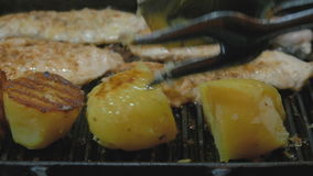 The cook fries potatoes and turkey fillets on the grill. Very tasty and mouth-watering. Close-up. View from above stock video footage