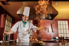 Cook fries vegetables on a kitchen. Kitchen hell. Japanese cook frying a vegetarian meal in burning flame of spirit on restaurant kitchen Royalty Free Stock Photos