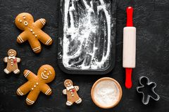 Cook gingerbread for new year 2018. Gingerbread man, rolling pin, flour on black background top view Royalty Free Stock Images