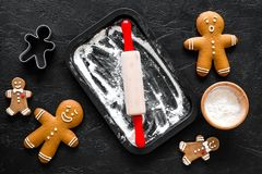 Cook gingerbread for new year 2018. Gingerbread man, rolling pin, flour on black background top view Royalty Free Stock Photos