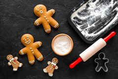 Cook gingerbread for new year 2018. Gingerbread man, rolling pin, flour on black background top view Stock Image