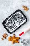 Cook gingerbread for new year 2018. Gingerbread man, rolling pin, flour on stone background top view Royalty Free Stock Photography