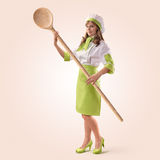 Cook girl with a big wooden spoon. On a beige background Royalty Free Stock Photography