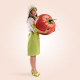 Cook girl holding a large tomato Royalty Free Stock Image