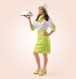 Cook girl with restaurant cloche or food tray. On a beige background Stock Image