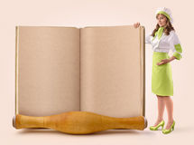 Cook girl shows a page of an old book Royalty Free Stock Image