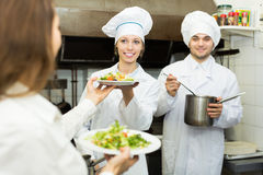 Cook gives to waitress plates Stock Photography