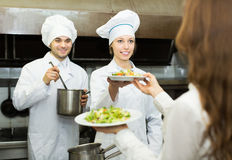 Cook gives to waitress plates Royalty Free Stock Images