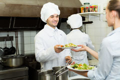 Cook gives to waitress plates Royalty Free Stock Photos