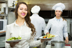 Cook gives to waitress plates Royalty Free Stock Image