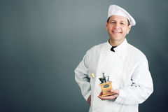 Cook with a grinder. Portrait of an aged professional male cook. Shot in a studio Stock Images