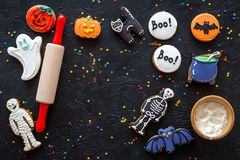 Cook halloween gingerbread cookies bat, skeleton, ghost. Sweets near rolling pin on black background top view copyspace stock images