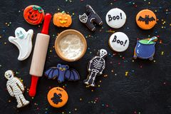 Cook halloween gingerbread cookies bat, skeleton, ghost. Sweets near rolling pin on black background top view copyspace royalty free stock images