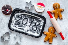 Cook gingerbread for new year 2018. Gingerbread man, rolling pin, flour on black background top view Stock Photo