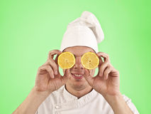 Cook with halves of lemon. On his eyes on green  background Royalty Free Stock Images