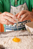 Cook hand cracking an egg into a pile of flour. Royalty Free Stock Photos
