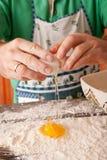 Cook hand cracking an egg into a pile of flour. Royalty Free Stock Photos