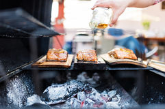 Cook hand pouring brandy on salmon. Image of a grill with salmon filet on wooden plank. The cooks is pouring aromatic alcohol on the fish for a stronger flavor stock photo