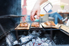 Cook hand pouring brandy on salmon. Image of a grill with salmon filet on wooden plank. The cooks is pouring aromatic alcohol on the fish for a stronger flavor royalty free stock photo