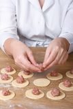 Cook hands closeup on round dough puts meat filling Stock Image