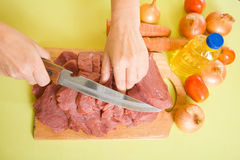 Cook hands cutting beef Royalty Free Stock Photography