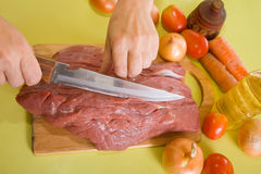 Cook hands cutting beef Stock Photo
