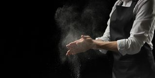 Cook hands in flour on a black background banner. Making pizza, pasta, bread baking and sweets. With an empty space for advertisin. G stock photo