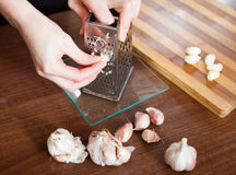 Cook hands  grating garlic with grater Royalty Free Stock Photos