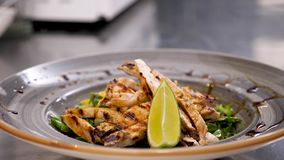 Cook hands placing a piece of lime on avocado salad with grilled meat. And seasoning it with seeds stock video footage