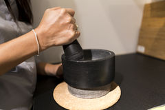 Cook hands pounding something using mortar and pestle Royalty Free Stock Photo