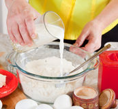 Cook hands pouring milk into flour Stock Photo