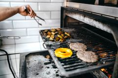 Cook hands prepares smoky meat on grill oven Royalty Free Stock Photography