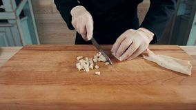 Cook hands is slicing of boiled squid. One of the stages of cooking calamaries. seafood restaurant top view. Cook hands is slicing of boiled squid stock footage